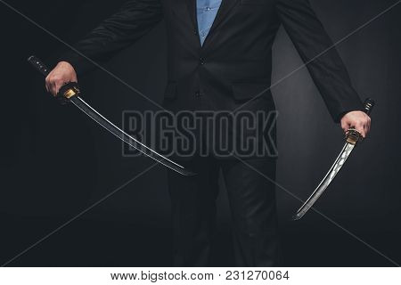 Crppped Shot Of Man In Suit With Dual Katana Swords On Black