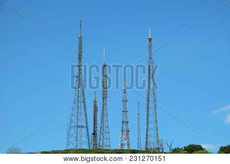 Many Steel Transmission Towers On The Green Hill With Blue Sky Background