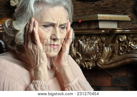 Portrait Of Senior Woman With Headache At Home