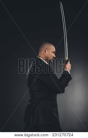 Side View Of Mature Yakuza Member In Suit With Katana Sword On Black