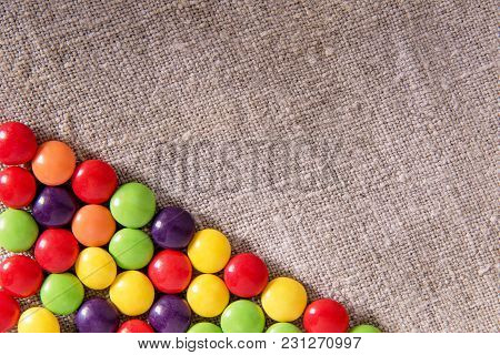 Delicious Chocolate Candy In A Colored Glaze On A Gray Textural Fabric With Copyspase