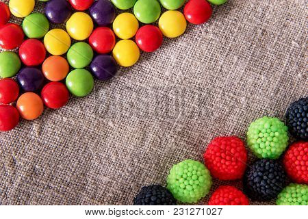 Delicious Chocolate Candy In A Colored Glaze With Color Fruit Sweets On A Gray Textural Fabric With