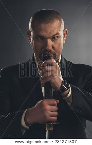 Close-up Portrait Of Adult Man In Suit With Katana Sword On Black