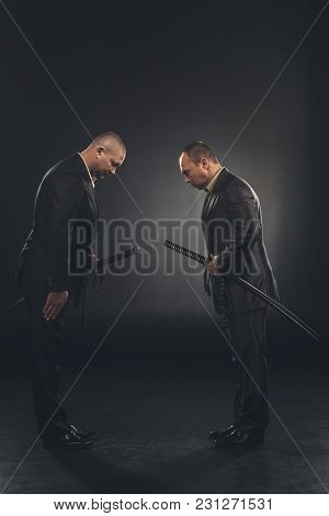Side View Of Yakuza Members In Suits Bowing To Each Other Isolated On Black