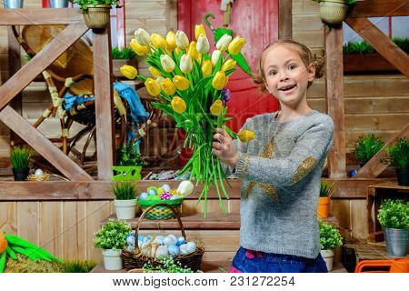 Happy little girl  with a large bouquet of tulips standing on the porch of a wooden house. Easter holiday.