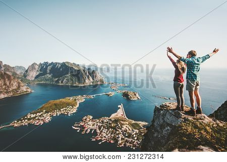 Happy Couple Love And Travel Raised Hands On Cliff In Norway Man And Woman Family Travelers Lifestyl