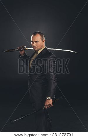 Handsome Man In Suit With Katana Sword Isolated On Black