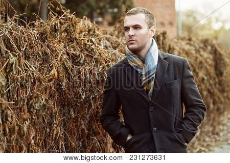 Seasonal autumn fashion. Portrait of a handsome man wearing black coat, and a scarf.  Autumn nature.