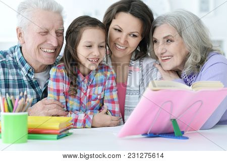 Little Cute Girl With Mother And Grandparents  Studying At  Home