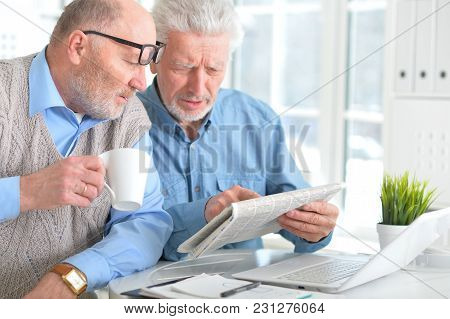 Two Senior Men Sitting At Table And Reading Newspaper