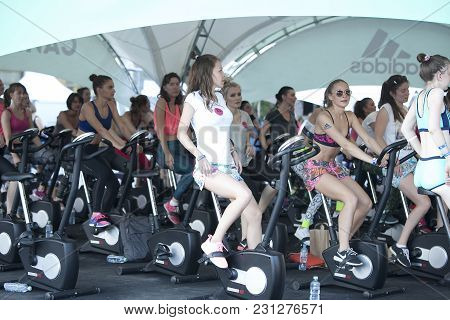 Moscow, Russia - June 23, 2016: Girl With Adidas Logo On The Hand Doing Exercise On The Exercise  Bi