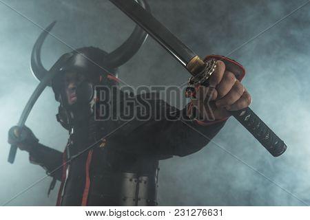 Close-up Shot Of Samurai In Armor With Dual Katana Swords On Dark Background With Smoke
