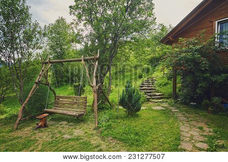 Swinging Bench In The Garden. Natural Wood