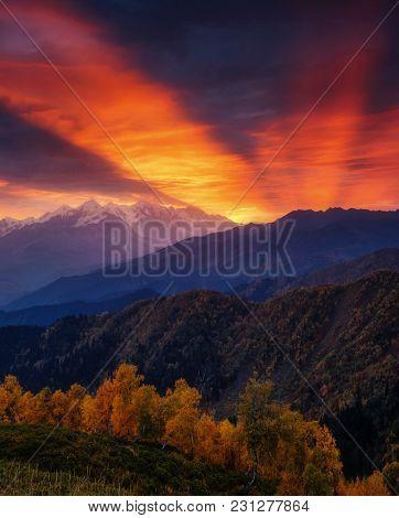 Fantastic red sunbeams with overcast sky at the foot of Mt. Ushba. Dramatic morning scene. Location Upper Svaneti, Mestia, Georgia, Europe. High Caucasus ridge. Warm toning effect. Beauty world.