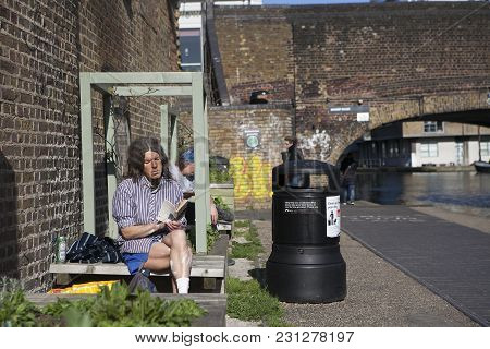 London - August 27, 2016: A Old Man With Long Hair In Shorts Reading A Book, Sitting On A Bench In T