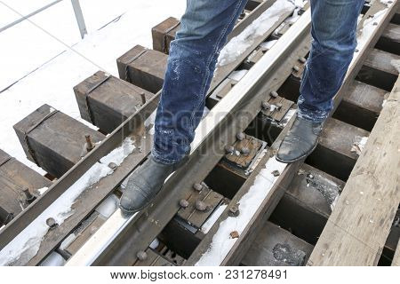 Men's Legs In Jeans And Boots Are The Railway. Walk On The Rails. Concept: Loneliness, Travel, The R