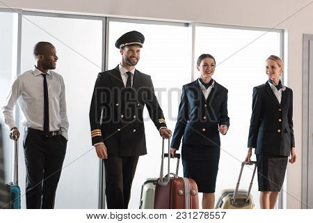 Happy Aviation Personnel Team Walking By Airport Loggy With Suitcases
