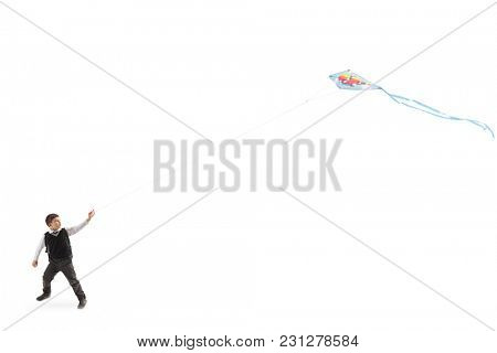 Full length profile shot of a schoolboy flying a kite isolated on white background