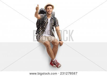Tourist sitting on a panel and making a thumb up gesture isolated on white background