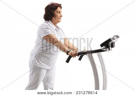 Mature woman walking on a treadmill isolated on white background