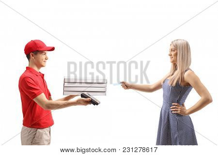 Teenage pizza delivery boy holding a payment terminal with a young woman giving him a credit card isolated on white background