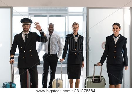 Young Aviation Personnel Team With Suitcases At Airport After Flight