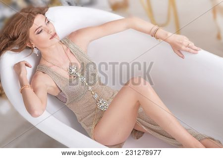 Portrait Of Beautiful Young Woman With Jewelry Lying In Bathtub