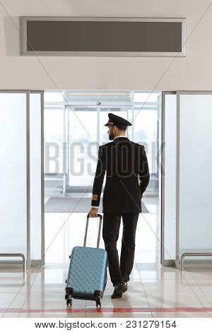 Back View Of Young Pilot With Suitcase At Departure Area