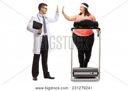 Full length profile shot of a doctor high-fiving an overweight woman exercising on a treadmill isolated on white background