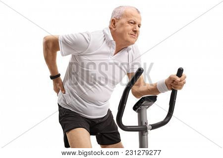 Mature man riding an exercise bike and experiencing back pain isolated on white background