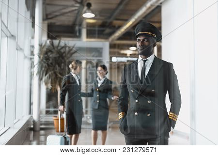 Thoughtful Young Pilot In Airport With Stewardesses Before Flight