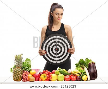 Fitness girl holding a target behind a table with fruit and vegetables isolated on white background