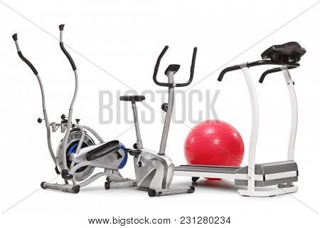 Exercise machines and a pilates ball isolated on white background