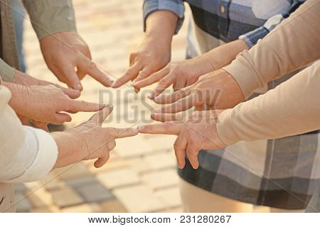 Senior people from care home putting hands together as symbol of unity outdoors