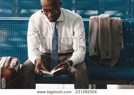 Businessman Reading Book While Waiting For Flight At Airport Lobby