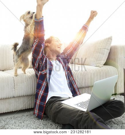 happy guy exults with his dog sitting near the sofa in the livin