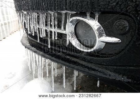 Frozen Car Close Up. Icicles On The Front Bumper.