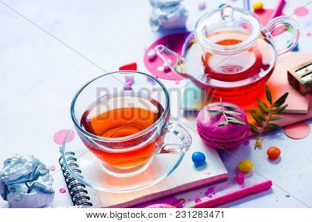 Teapot And Glass Cup Backlight Vibrant Close-up. Confetti And Macarons On A Light Background. Tea Pa
