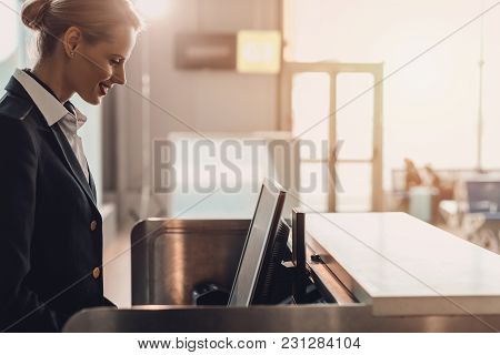 Side View Of Attractive Young Airport Worker At Workplace At Airport Check In Counter