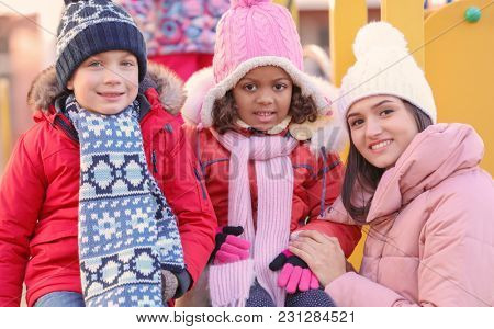 Young woman with little kids on playground. Child adoption