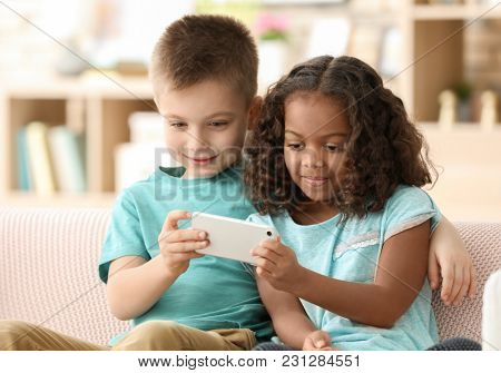 Cute children with smartphone indoors. Child adoption