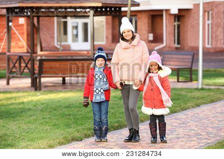 Young woman with little kids outdoors. Child adoption
