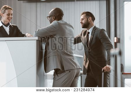 Businessmen Standing At Airport Reception To Buy Tickets
