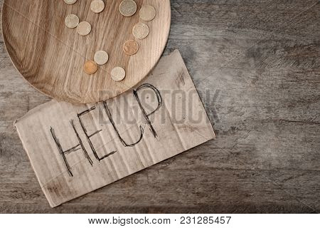 Piece of cardboard with word HELP and coins on wooden background. Poverty concept