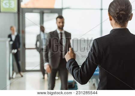 Businesswoman Waiting For Partner With Name Sign On Paper At Airport