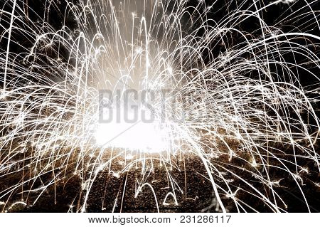 Abstract Image Of An Exploding Firework On The Ground In The Night