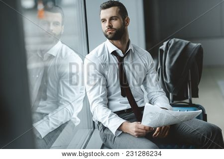 Handsome Young Businessman With Newspaper Waiting For Flight At Airport Lobby