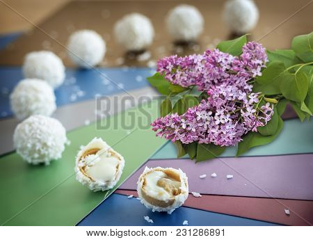 Still Life: On The Table Delicious Cookies With Cream Filling And A Branch Of Flowering Lilac On A B