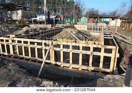 Kyiv, Ukraine - March, 16, 2018:  Contactors Building T-shaped Concrete Foundation With Slabs And Ir