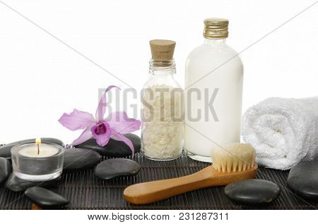 Spa setting with pink orchid, black stones. Rolled towel ,candle, brush ,salt in bottle, oil on mat background